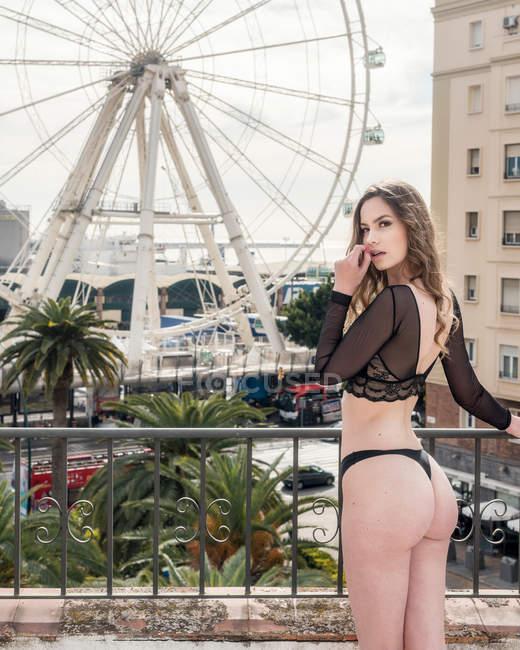Brunette woman wearing alluring black underwear standing on balcony with Ferris wheel on background — Stock Photo