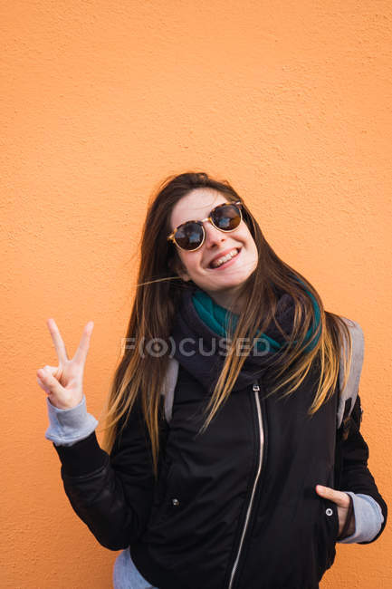 Excited woman showing victory sign against orange wall — Stock Photo