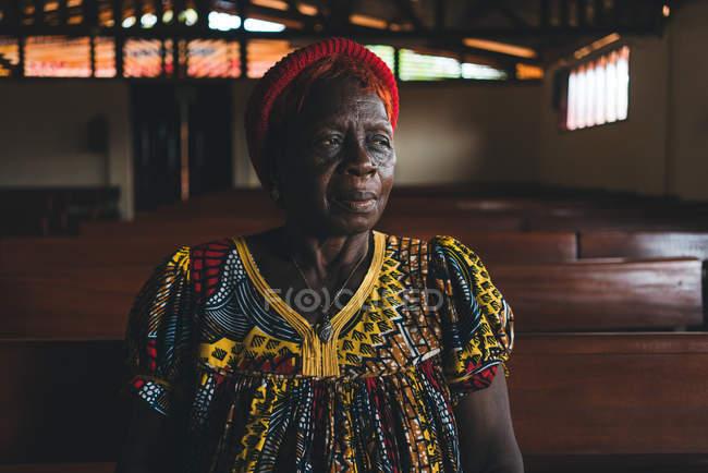 КАМЕРУН - Африка - 5 апреля 2018 года: Старшая африканская женщина в традиционной одежде стоит в церкви и смотрит в сторону — стоковое фото