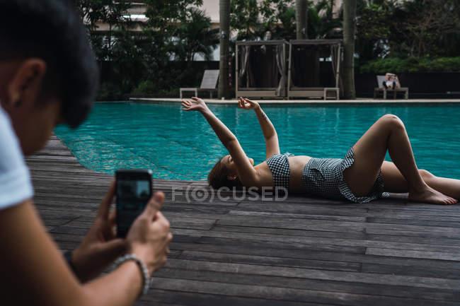 Photographer taking photo of Asian woman lying at pool edge — Stock Photo