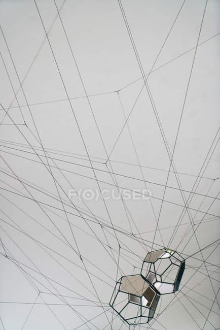 Zwei abstrakte geometrische Figuren, die an verworrenen Fäden auf grauem Hintergrund hängen — Stockfoto