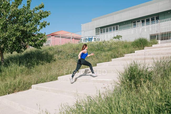 Sporty young woman running upstairs outdoors — Stock Photo