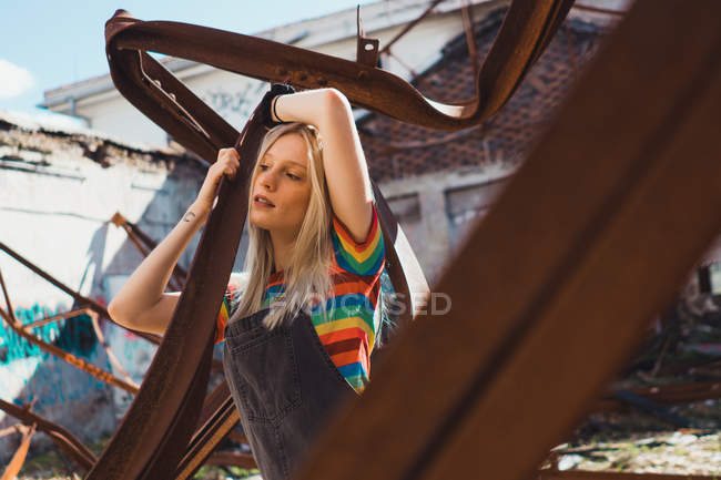 Sensual young girl in modern outfit leaning on grungy metal fixture outside — Stock Photo