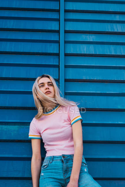Thoughtful young blonde woman leaning on blue wall on street and looking away — Stock Photo