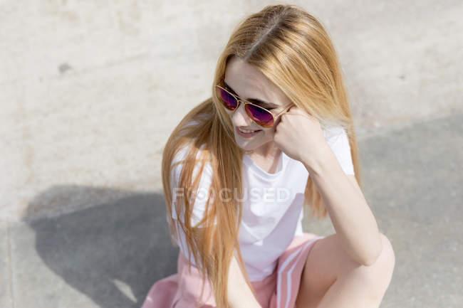 Blonde teenage girl in skirt sitting on ground — Stock Photo