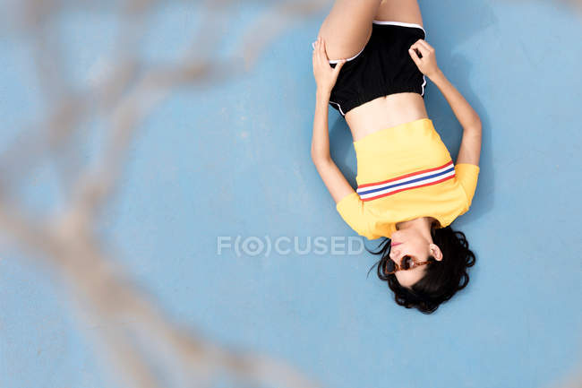 Attractive slim female in sports clothes and sunglasses lying on blue background — Stock Photo