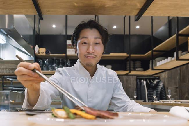 Chef preparando el plato con palillos en el restaurante - foto de stock