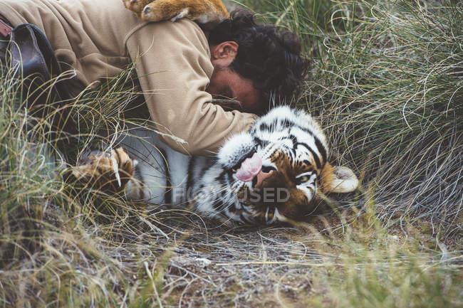 Hombre acariciando tigre mientras está acostado en la hierba - foto de stock
