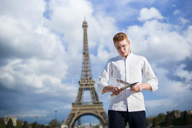 Red-Hair cook with knives standing in front of Eiffel Tower in Paris — Stock Photo