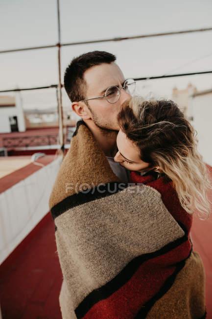 Paar umarmt sich mit Decke auf Terrasse — Stockfoto