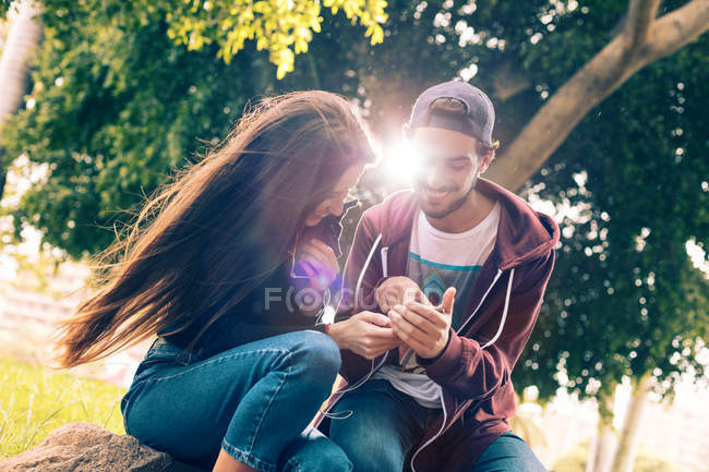 Laughing young couple sitting with smartphone in park — Stock Photo