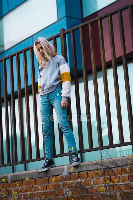 Hübsche blonde Frau steht am Zaun vor modernen Häusern — Stockfoto