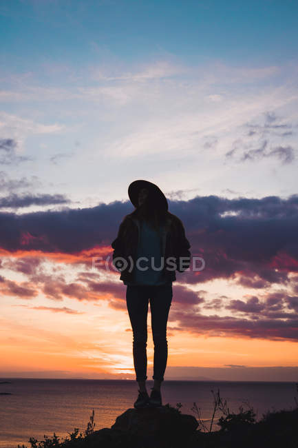 Woman in hat standing on coast under evening sky — Stock Photo