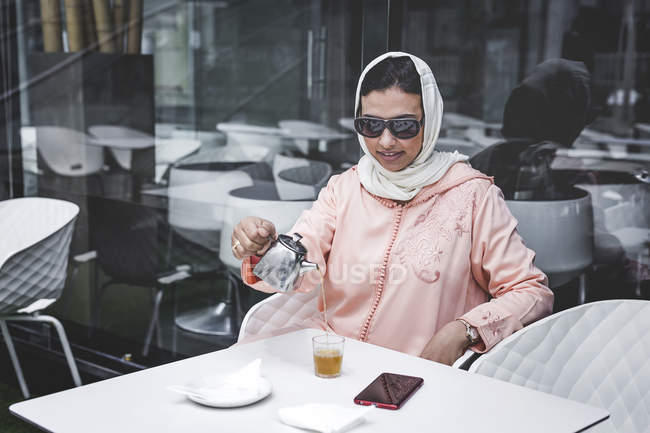 Marokkanerin mit Hijab und typisch Arabisch Kleid Gießen Tee im café — Stockfoto