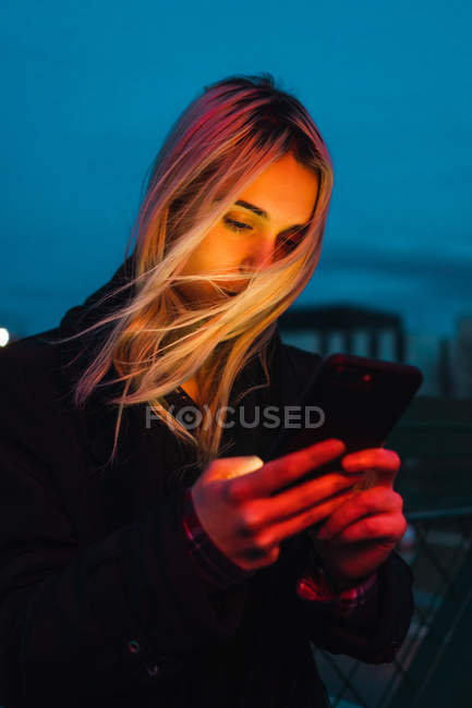 Blonde woman using smartphone on street in dusk — Stock Photo