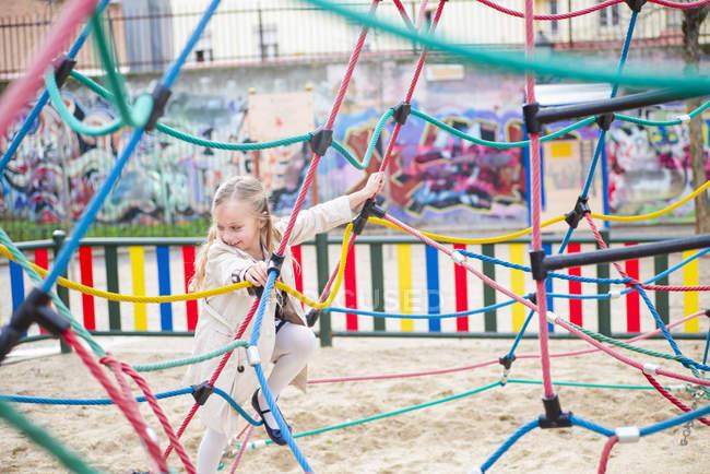 Jovencita alegre trepando sobre cuerdas en el patio de recreo - foto de stock