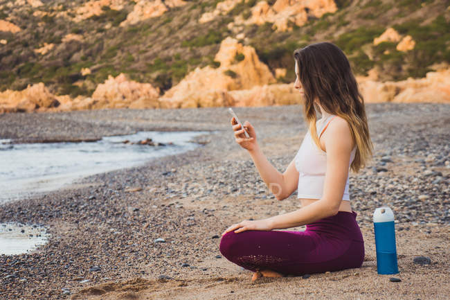 Женщина в спортивной одежде сидит на берегу моря и просматривает смартфон — стоковое фото