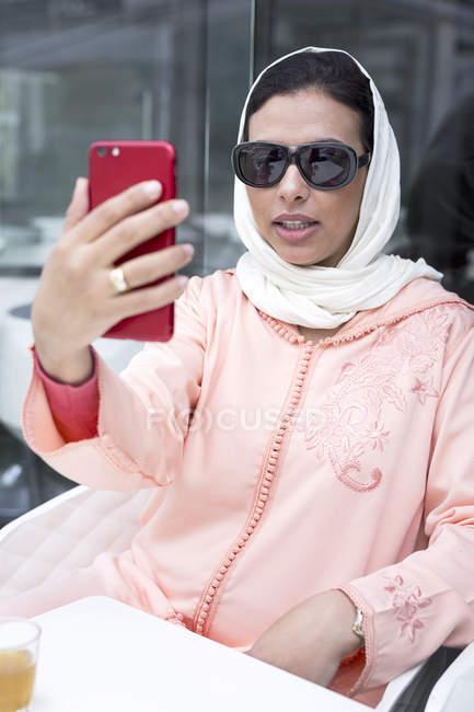 Elegante Marokkanerin mit Hijab und typische arabische Kleidung nehmen Selfie im café — Stockfoto