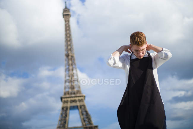 Red-Hair cook wearing black apron standing in front of Eiffel Tower in Paris — Stock Photo