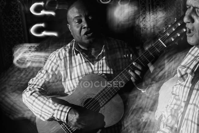 Musiker spielt Gitarre und singt im Nachtclub, Schwarz-Weiß-Aufnahme mit Langzeitbelichtung — Stockfoto