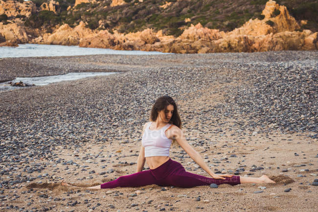 Fit woman sitting and stretching in string pose on shore at ocean — Stock Photo