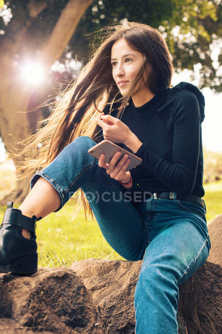 Young woman sitting on rock and holding smartphone in park — Stock Photo