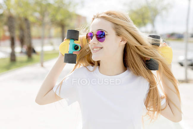 Blonde girl walking with penny board — Stock Photo