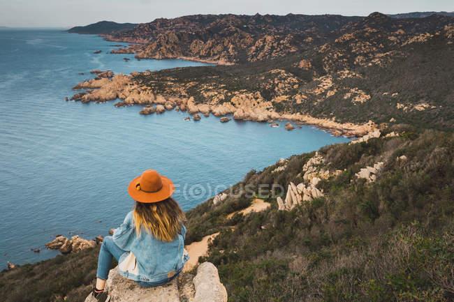 Жінка на скелі на океан і, дивлячись на вид — стокове фото
