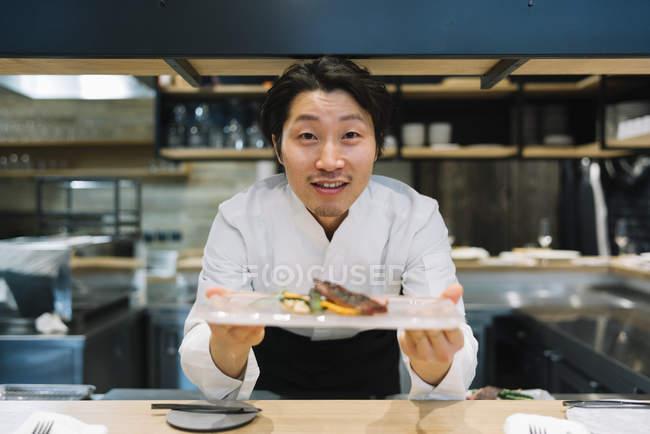 Улыбаясь шеф-повар показаны тарелку с едой в ресторане — стоковое фото