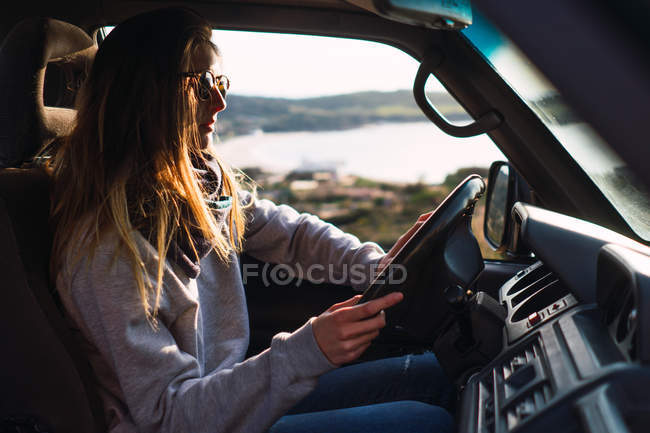 Young woman in sunglasses driving car in nature — Stock Photo