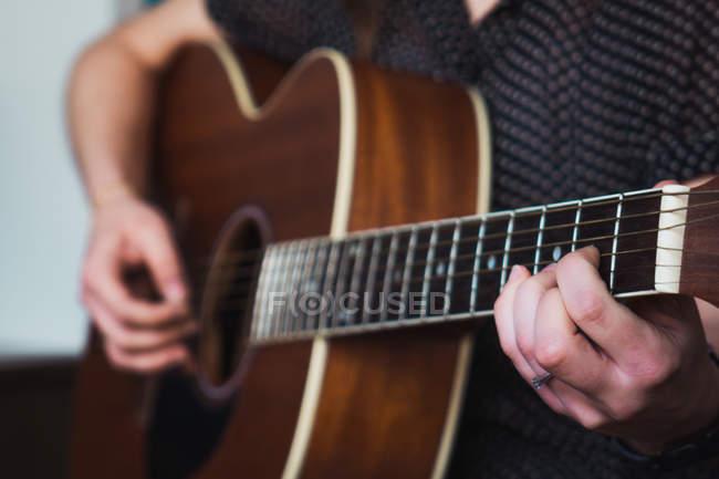 Nahaufnahme menschlicher Hände beim Spielen einer akustischen Gitarre — Stockfoto