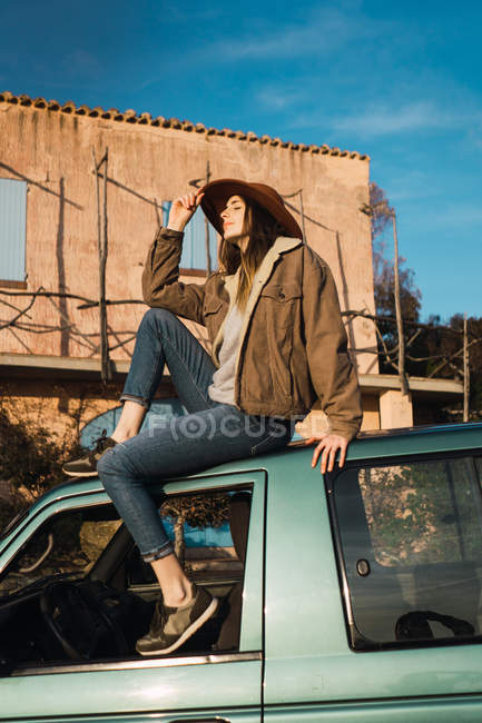 Pretty tourist woman in hat sitting on car roof in front of building — Stock Photo