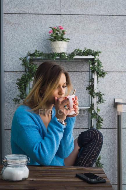 Junge Frau mit Kaffee auf Balkon chillen — Stockfoto