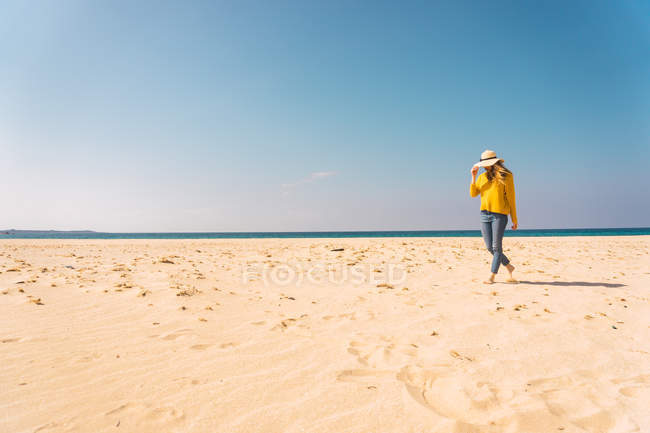 Woman in bright yellow sweater standing on sandy beach — Stock Photo