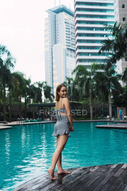 Ritratto di donna sorridente in piedi a bordo piscina — Foto stock