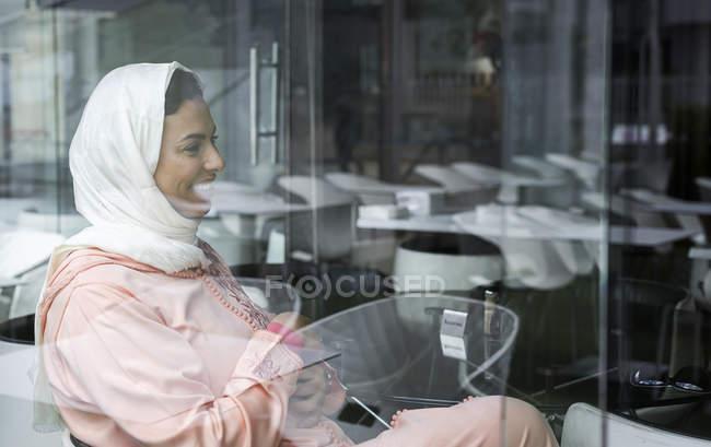 Rir mulher marroquina com hijab e típico árabe vestido sentado no café — Fotografia de Stock