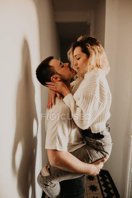 Страстный мужчина и женщина обнимаются и целуются у стены дома — стоковое фото