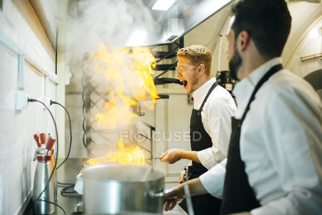 Excited cook making a flambe in restaurant kitchen with colleague watching — Stock Photo