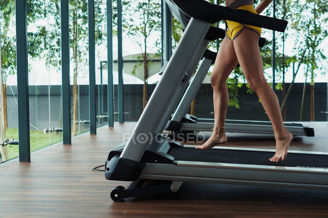 Female legs running on race track in gym — Stock Photo