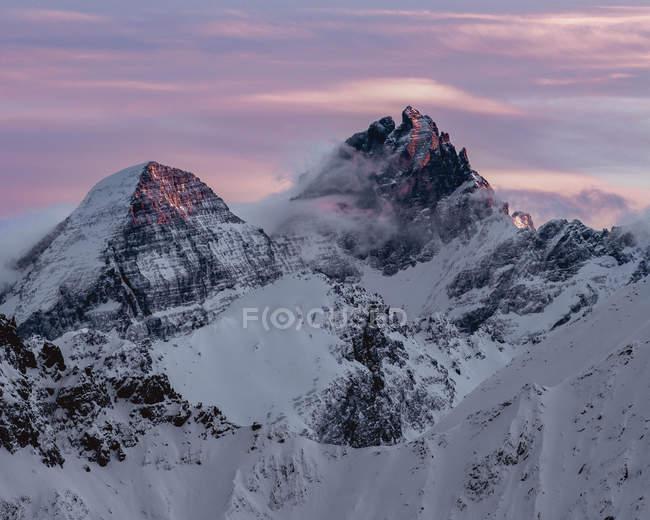 Montagne coperte di neve sotto il cielo drammatico al tramonto — Foto stock