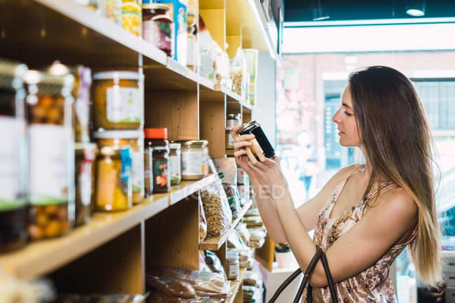 Jeune femme ramasser pot de confiture en magasin — Photo de stock
