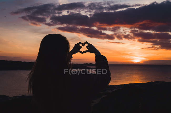 Silhouette of woman standing at ocean at sunset and gesturing heart with fingers — Stock Photo