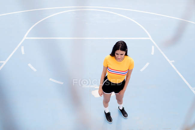 Young woman standing on sports ground — Stock Photo
