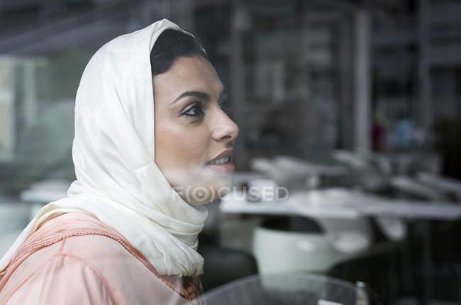 Nachdenklich Marokkanerin mit Hijab sitzt hinter Fensterscheibe — Stockfoto