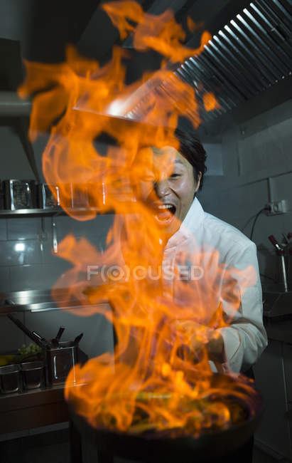 Excited cook making a flambe in restaurant kitchen — Stock Photo