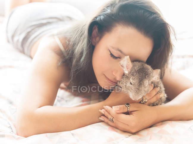 Jovem mulher deitada na cama com a chinchila — Fotografia de Stock