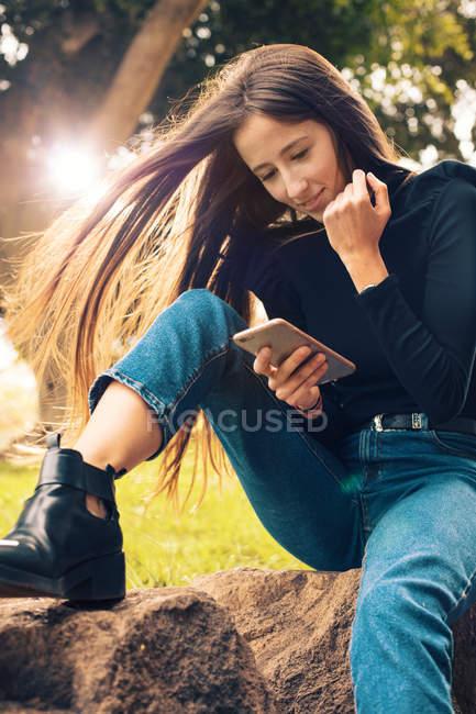 Giovane donna sorridente seduta sulla roccia e utilizzando smartphone nel parco — Foto stock