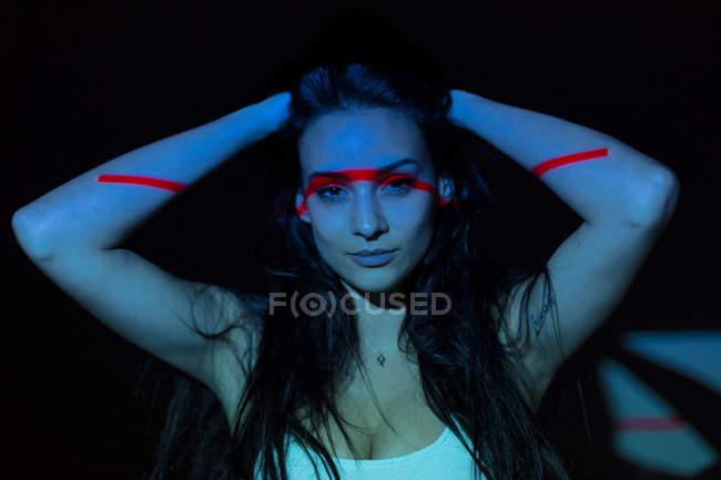 Giovane donna attraente con linea rossa sul viso e sul corpo guardando la fotocamera su sfondo scuro — Foto stock