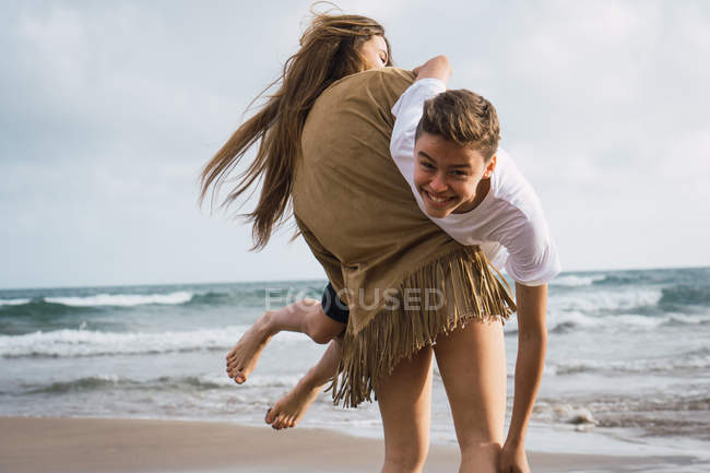 Laughing teenage friends fooling around on seashore in summer — Stock Photo