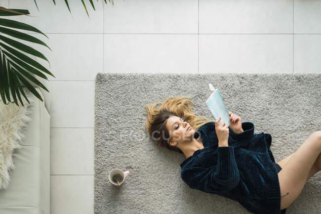 Жінка з кави і книги, лежачи на килимі в парковій зоні — стокове фото